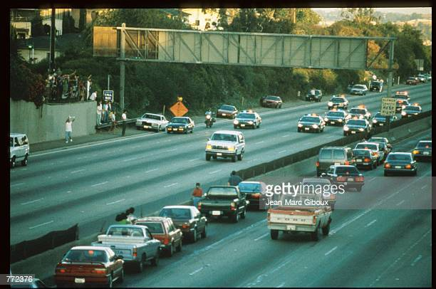 Motorists stop and wave as police cars pursue the Ford Bronco driven by Al Cowlings carrying fugitive murder suspect OJ Simpson on a 90minute...