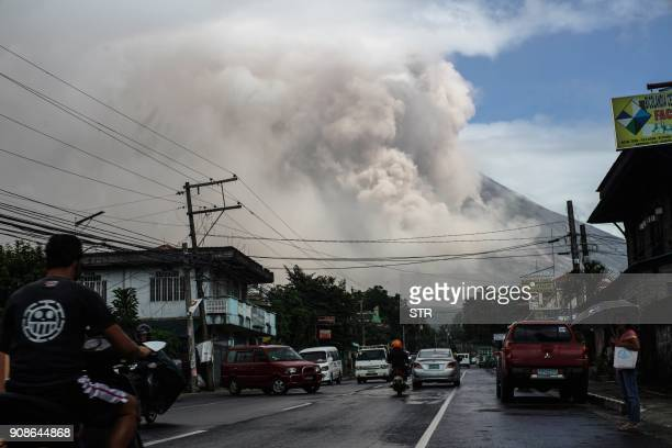 TOPSHOT Motorists travel on a highway as Mount Mayon shot up a giant mushroomshaped cloud as it continues to erupt near Camalig town near Legazpi...
