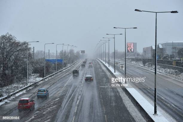 Motorists travel on a snowy day along the M1 Highway on the outskirts of London on December 10 2017 Heavy snow fell across northern and central parts...