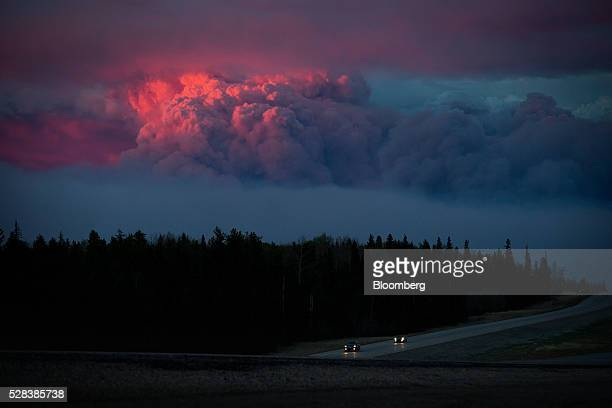 Motorists travel south on Alberta Highway 63 as the setting sun illuminates a huge plume of smoke from wildfires burning in the distance rising over...
