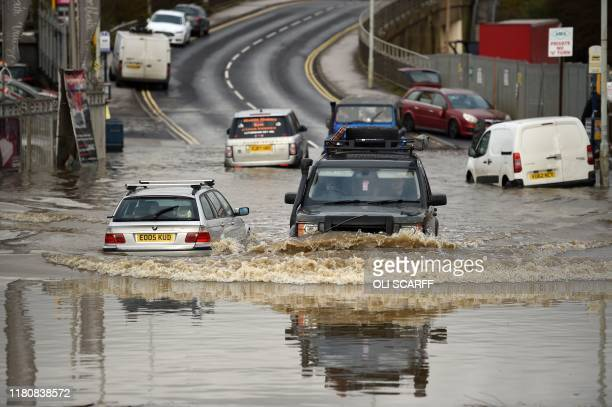 Motorists travel through floodwaters in Rotherham northern England on November 8 following flash flooding the previous day Over a month's worth of...
