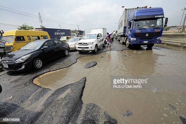Motorists try to avoid waterlogged potholes on Apapa Oshodi expressway that leads to Apapa ports West Africa's busiest and largest container terminal...