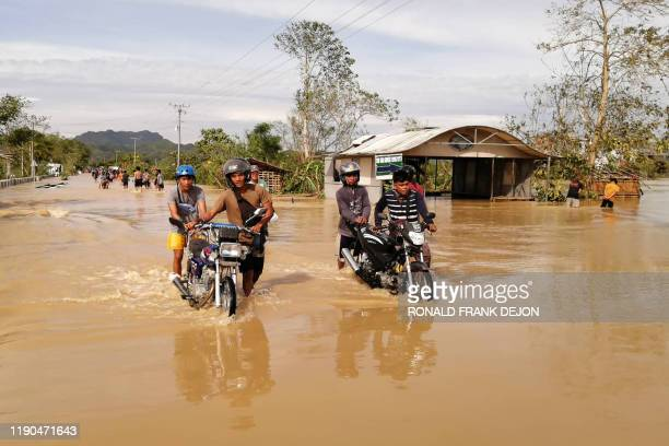 Motorists wade through a flooded highway caused by heavy rains due to typhoon Phanfone in Ormoc City Leyte province in central Philippines on...