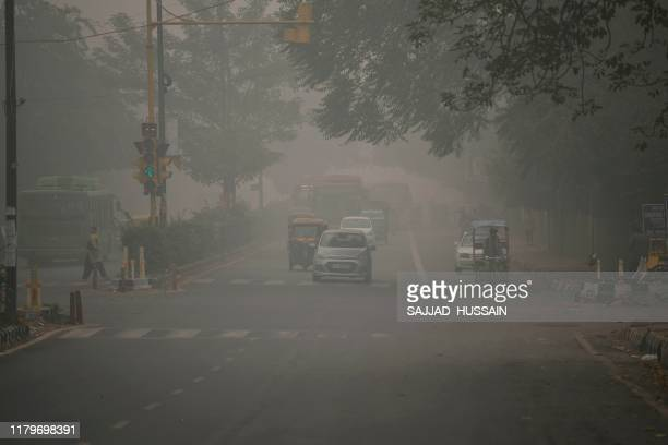 Motorists wait for a green light at a road junction under heavy smog conditions, in New Delhi on November 3, 2019. - India's capital New Delhi was...