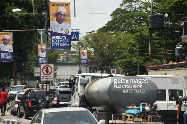 Motorists wait in a traffic jam under banners bearing a portrait of Nigeria's President Muhammadu Buhari who is on official visit to Lagos on March...