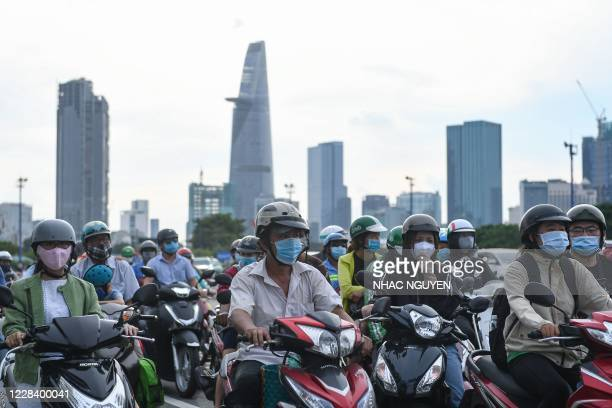 Motorists wait on their motorcycles at a traffic light during rush hour in Ho Chi Minh City on September 8, 2020.