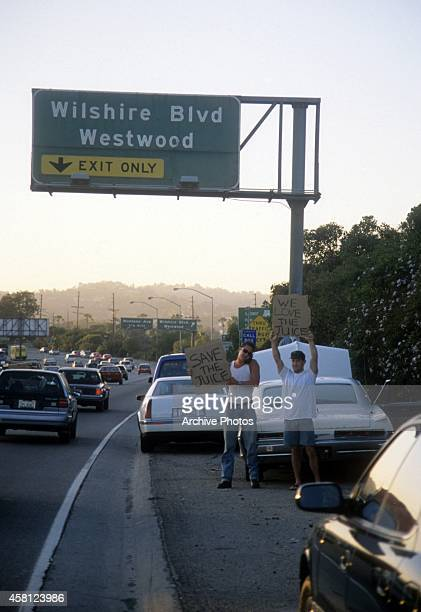 Motorists wave signs as police cars pursue the Ford Bronco driven by Al Cowlings, carrying fugitive murder suspect O.J. Simpson, on a 90-minute...