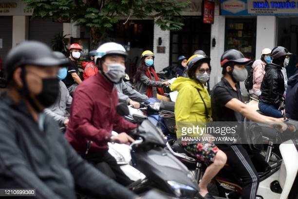 Motorists wearing face masks wait at a trafficlight in Hanoi on April 23 as Vietnam eased its nationwide social isolation effort to prevent the...