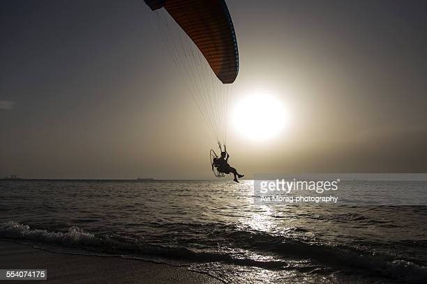 Motorized paraglider flying over sea