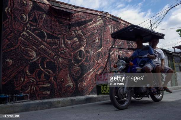 A motorized tricycle drives past a mural depicting guns at a village in Manila Philippines on Monday February 12 2018 Philippine President Rodrigo...