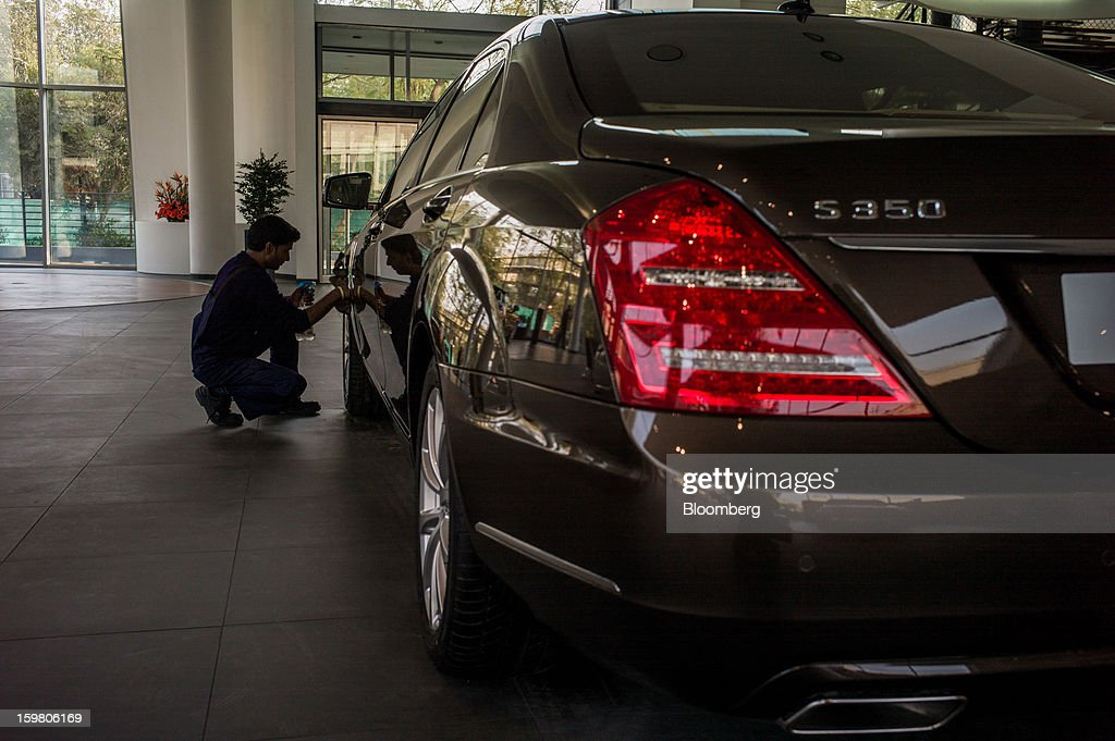 Motors Ltd. employee cleans a Daimler AG Mercedes-Benz S350 vehicle as it sits on display inside the company's newly opened Mercedes-Benz India flagship dealership in New Delhi, India, on Saturday, Jan. 19, 2013. The Indian Finance Ministry projects Asia's third-largest economy will expand as little as 5.7 percent in the 12 months to March 31, which would be the weakest pace in a decade. Photographer: Sanjit Das/Bloomberg via Getty Images