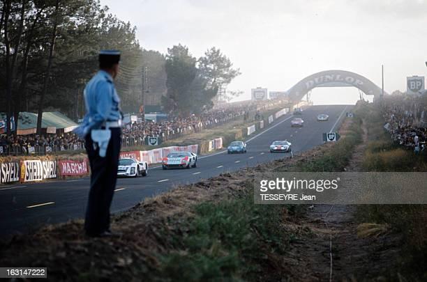 Motorsport 24 Hours Of Le Mans 1966 Sur le circuit du Mans un gendarme en uniforme sur le bord de la piste regardant les voitures