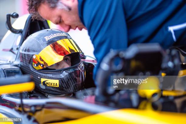 motorsport crew member helping formula driver - grand prix motor racing stock pictures, royalty-free photos & images