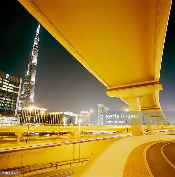 Motorway and flyover connections in Dubai with view of Burj Khalifa at night.