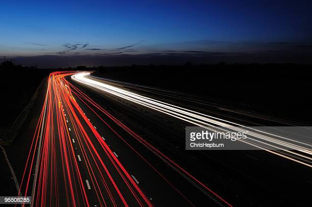motorway lights at twilight - light trail stock photos and pictures