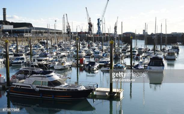Motoryachsts and sailing cruiers sits moored to pontoons in the harbour in St Helier on the British island of Jersey on November 8 2017 Jersey is a...