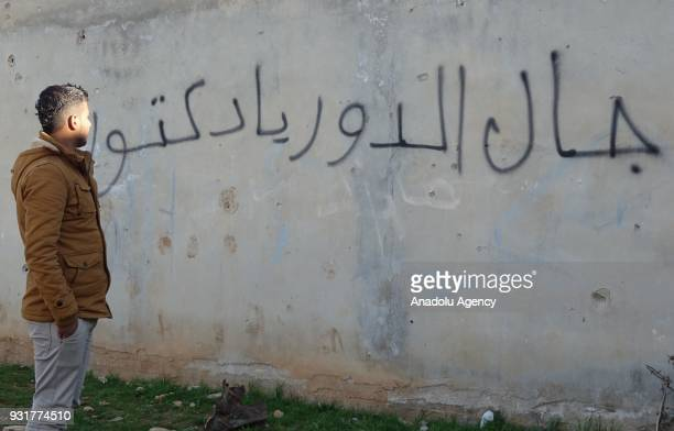 Mouawiya Syasneh the boy who started the civil rebellion gestures near the Graffiti reads Doctor your turn during and an exclusive interview in Daraa...