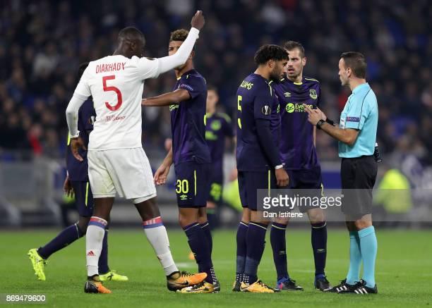 Mouctar Diakhaby of Lyon signals to the referee for a card as refeere Orel Grinfeld speaks with Morgan Schneiderlin of Everton and Ashley Williams of...