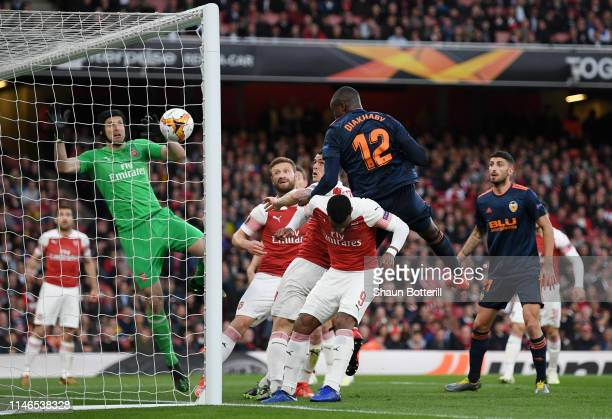 Mouctar Diakhaby of Valencia outjumps Alexandre Lacazette and Granit Xhaka of Arsenal as he scores his team's first goal past Petr Cech during the...