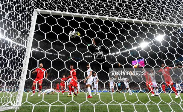 Mouez Hassen of Tunisia saves from a header from John Stones of England as Harry Kane prepares to follow up and score his team's first goal during...