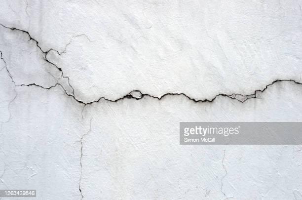 mouldy and cracked whitewashed wall - agrietado fotografías e imágenes de stock