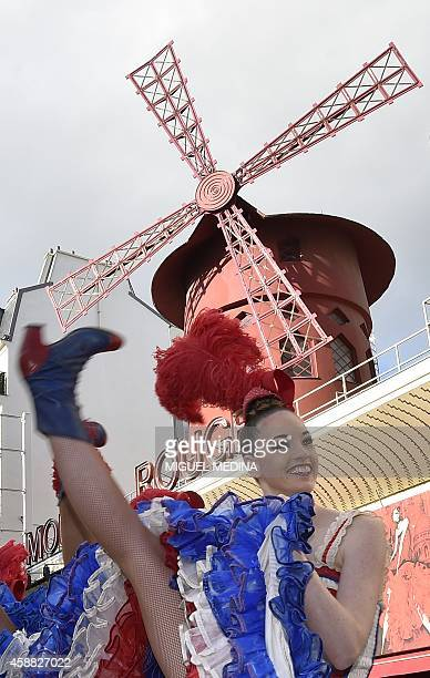 Moulin Rouge dancer performs with others on November 7 2014 outside the cabaret in Paris in a bid to break the record of the simultaneous demigrand...