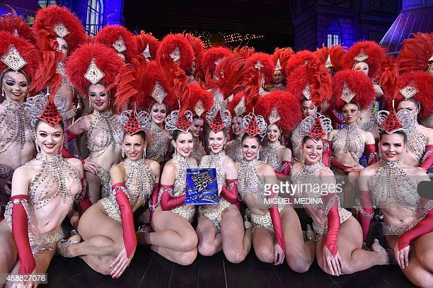 Moulin Rouge dancers pose on November 7 2014 with the 2015 Guinness book certificate after breaking the record of the simultaneous demigrand rond de...