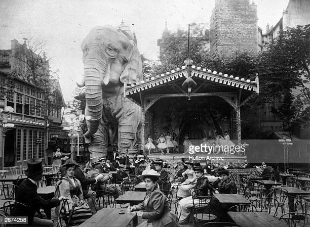 Moulin Rouge Montmartre Paris In the background a gigantic model elephant looms over a stage on which ballet dancers are posed