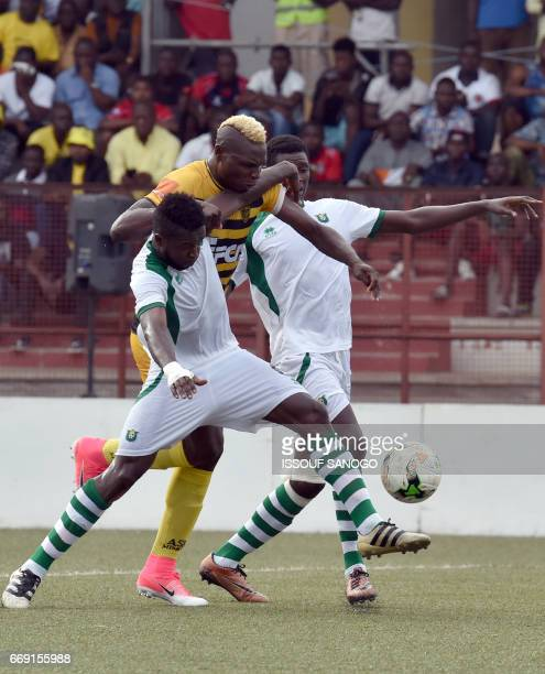 CF Mounana Dieu Donne Nkoume vies for the ball with Asec Abidjan's Aristide Bance during the qualifying football match for the group stage of the...