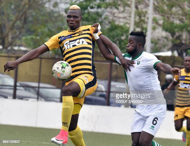 CF Mounana's Dieu Donne Nkoume vies for the ball with Asec Abidjan's Aristide Bance during the qualifying football match for the group stage of the...