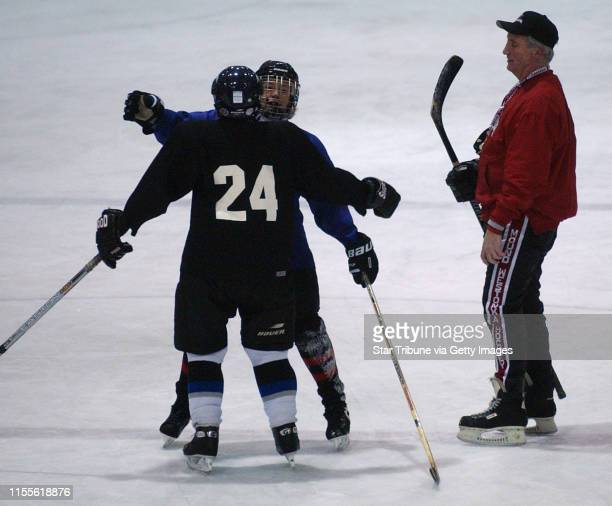 Mound Mn Weds Dec 10 2003Kerry Engel and Linda Dreyer hug as coach Mike Curti waits to drop the puck to start play in the hockey game during Curti's...