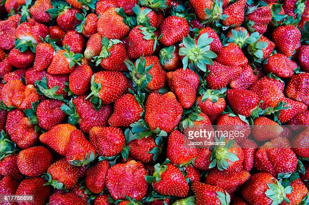 A mound of lush red strawberries for sale in a fresh food market.