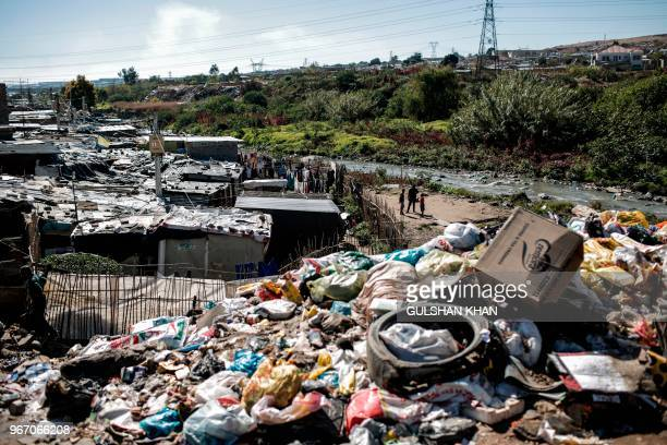 Mound of plastic and other waste rises up from the banks of the Jukskei River which runs through Alexandra Township in Johannesburg on June 3, 2018....