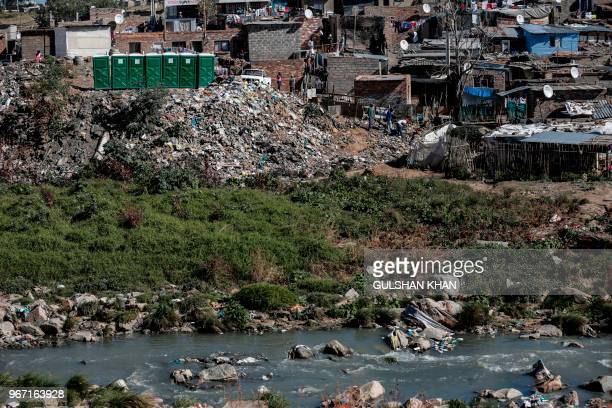 A mound of plastic and other waste rises up from the banks of the Jukskei River which runs through the Alexandra Township in Johannesburg on June 3...