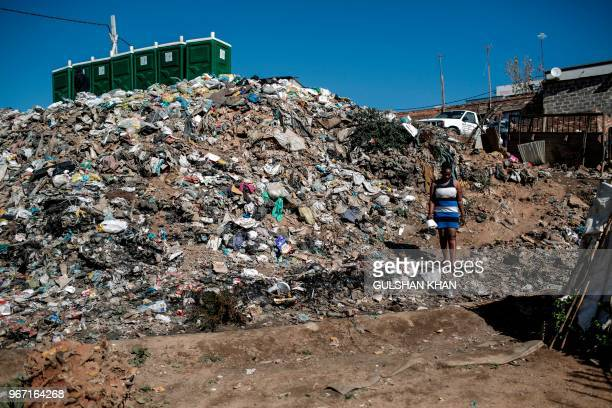 A mound of plastic and other waste rises up from the banks of the Jukskei River which runs through Alexandra Township in Johannesburg on June 3 2018...