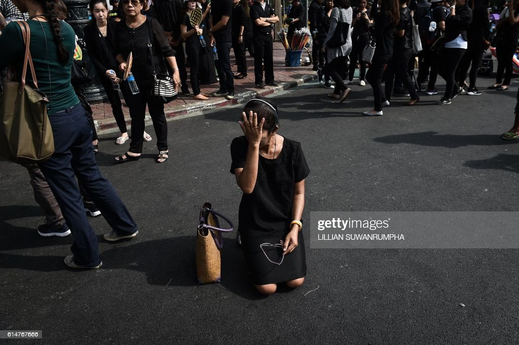 TOPSHOT - A mouner cries in the street whilst paying her respects to the late Thai King Bhumibol Adulyadej outside of the Grand Palace in Bangkok on October 15, 2016. Thailand's government has warned of a national shortage of black clothing, which is flying off shelves as a distraught nation mourns beloved late King Bhumibol Adulyadej. / AFP / LILLIAN