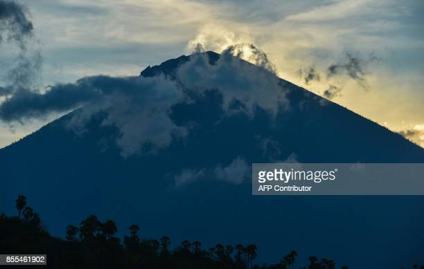 Mount Agung is during sunset in Amed beach in Karangasem on Bali island on September 29 2017 A rumbling volcano on the holiday island of Bali is...