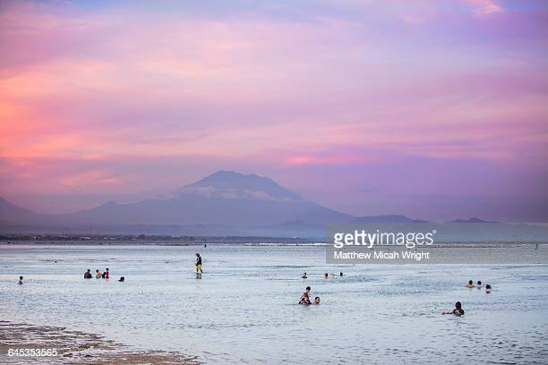 Mount Agung looms in the distance at sunset.