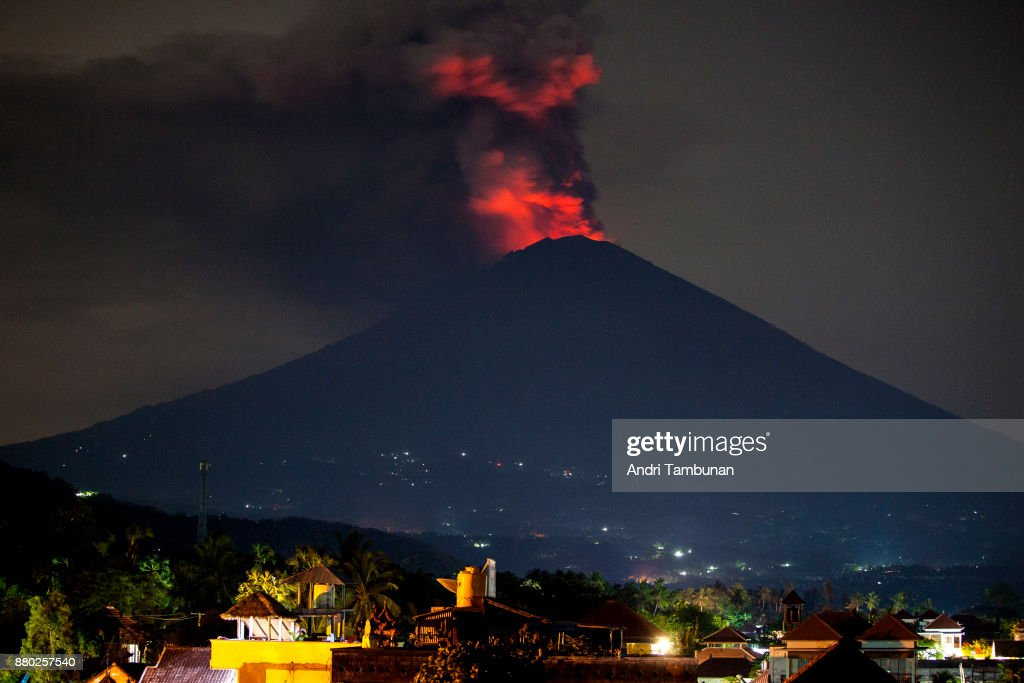 KARANGASEM, BALI, INDONESIA - NOVEMBER 27: Mount Agung spews volcanic ash into the sky at night on November 27, 2017 in Karangasem, Island of Bali, Indonesia. Indonesian authorities raised the state of alert to its highest level for the volcano, Mount Agung, after thick ash started shooting thousands of meters into the air with increasing intensity. Based on reports, as many as 100,000 villagers will need to leave the expanded danger zone while tens of thousands of tourists have been stranded due to airport closures.