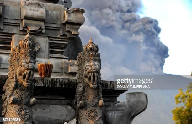 Mount Agung's eruption is seen next to a Balinese temple at Kubu subdistrict in Karangasem Regency on Indonesia's resort island of Bali on November...
