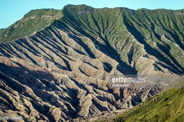 mount batok (2,470m), though lying adjacent to mount bromo. with a perfect triangular mountain top, rising from a sea of volcanic ash surrounding the mount bromo caldera. - shaifulzamri stock pictures, royalty-free photos & images