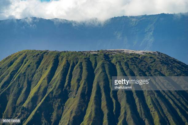 mount batok (2,470m), though lying adjacent to mount bromo. with a perfect triangular mountain top, rising from a sea of volcanic ash surrounding the mount bromo caldera. east java of indonesia. - shaifulzamri stock pictures, royalty-free photos & images