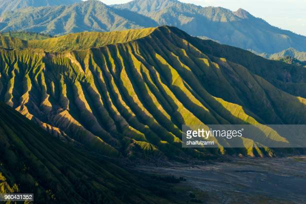 mount batok (2,470m), though lying adjacent to mount bromo. with a perfect triangular mountain top, rising from a sea of volcanic ash surrounding the mount bromo caldera. east java of indonesia. - vulkanlandschaft stock-fotos und bilder