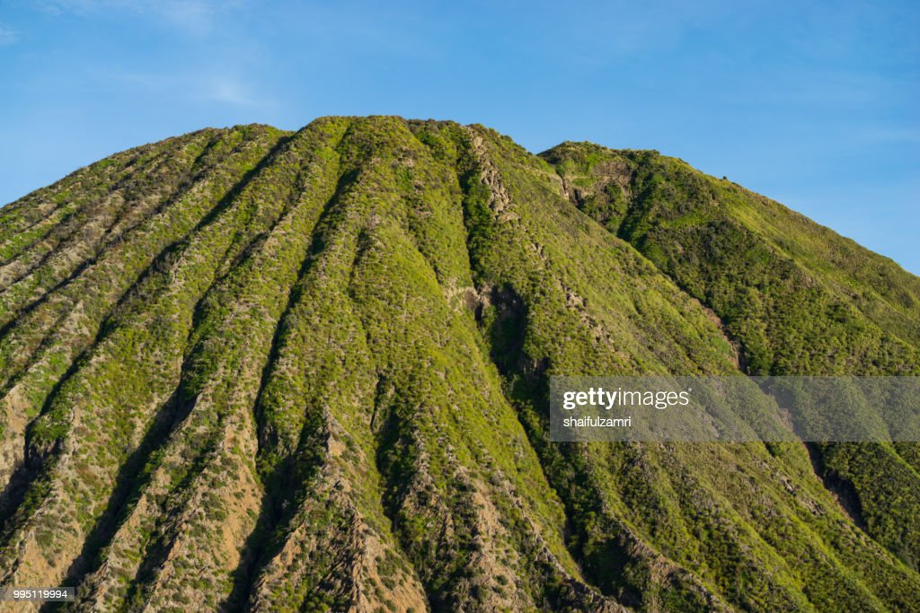 Mount Batok (2,470m), though lying adjacent to Mount Bromo. With a perfect triangular mountain top, rising from a sea of volcanic ash surrounding the Mount Bromo caldera. East Java of Indonesia. : Stock Photo