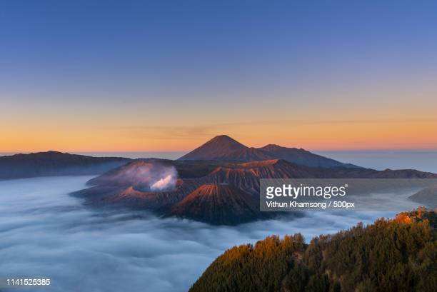mount bromo shrouded in clouds at dusk - east java province stock pictures, royalty-free photos & images