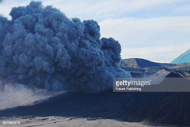 """Mount Bromo volcanic ash seen above the Cemoro Lawang village, where Tenggerese perform traditional dance called """"Ujung-Ujungan"""" on January 30, 2016..."""