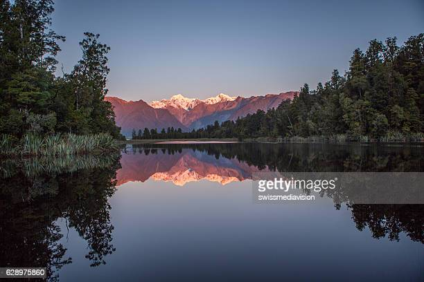 Mount Cook reflection in the mirror-like surface of the lake-sunset