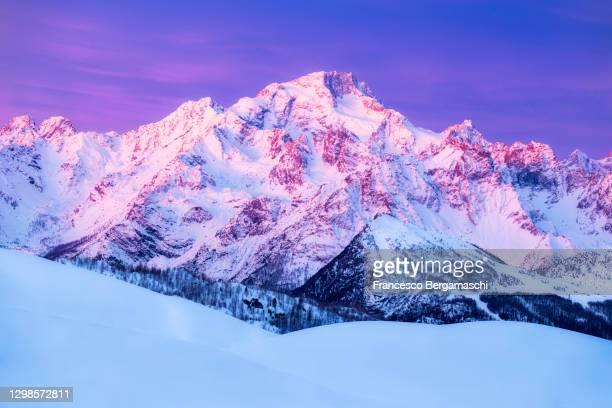 mount disgrazia illuminates by pink light at sunrise. - italia stockfoto's en -beelden