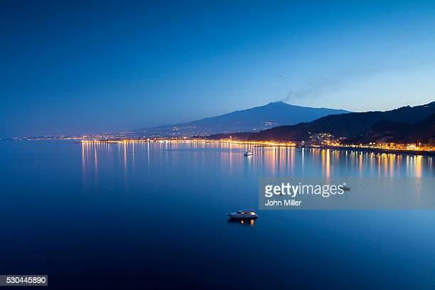 mount etna and giardini naxos at dusk, sicily, italy, mediterranean, europe - naxos sicily stock pictures, royalty-free photos & images