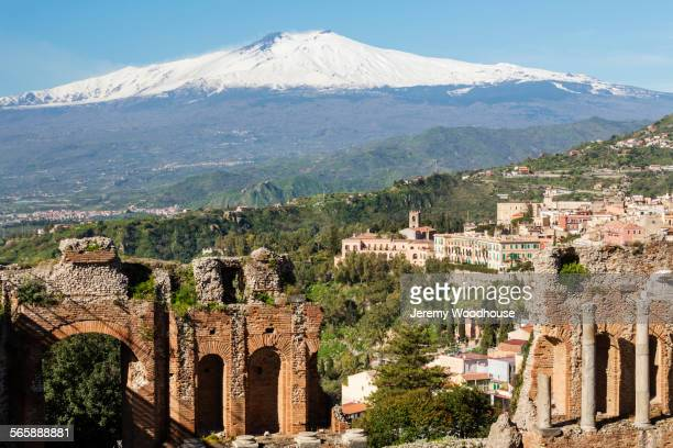 Mount Etna and Greek Theater ruins over Taormina cityscape, Messina, Sicily